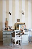 Desk and chair below hunting trophies hung on striped wallpaper