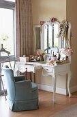 Traditional armchair with blue loose cover at white, antique-style dressing table
