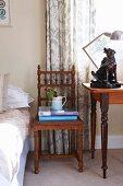 Antique, carved chair next to dog ornament on table
