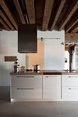 Kitchen island with corrugated metal fronts in loft-style apartment with rustic wooden ceiling