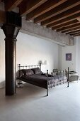Black metal bed with black bed linen in minimalist sleeping area of loft apartment with rustic wooden ceiling