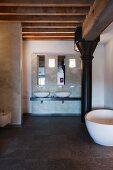 Minimalistischer Badbereich, im Hintergrund weisse Aufsatzbecken, seitlich freistehende Badewanne vor schwarzer Metallstütze unter Holzdeckenkonstruktion