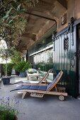 Liegestühle mit Polster auf Terrasse, vor industriellem Loft, Kräuterpflanzen und Bäume im Übertopf