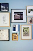Collection of framed drawings and photos around intercom unit on wall painted pale blue