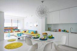 Offener Wohnraum in Weiss, Essplatz mit Klassiker Schalenstühlen gegenüber weisser Einbauküche, gelbe, runde Teppiche als Farbtupfer