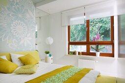 Schlafzimmer mit Doppelbett, Bettwäsche und Kissen in Weiss und Gelb, gegenüber Holzfenster mit weissen Rollos und Gartenblick