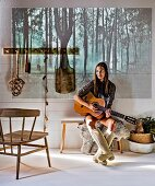 Young woman holding guitar sitting on bench; picture of forest projected on wall