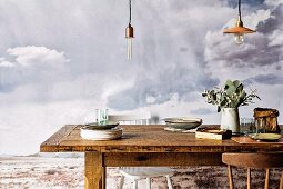 Stacked plates and vase on rustic table below vintage pendant lamps in front of picture of grey cloudy sky