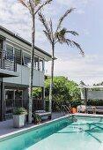 Palmen am Pool im Garten, vor zeitgenössischem Wohnhaus