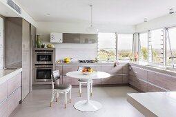 Klassiker Essplatz mit Tulip Table und gepolsterte Thonetstühle in moderner Einbauküche mit umlaufender Küchenzeile