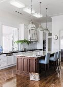 Fitted counter with marble worksurface on Colonial-style wooden base and upholstered bar stools below pendant lamps in elegant country-house kitchen