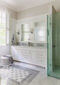 Fitted washstand, white base cabinets, mirrored wall units with sconce lamps and glazed shower area in elegant bathroom