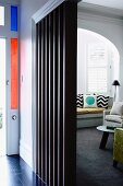 Stained glass elements around front door, sofa in living room window bay and black slatted wooden partition in foreground