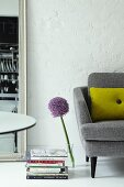 Retro sofa and allium in glass vase on floor