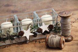 DIY-Windlichter mit adventlicher Deko aus Zapfen und weissen Holzsternen in länglichem Holztablett