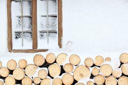 Verschneite Landhausfassade mit gestapeltem Brennholz unter Sprossenfenster