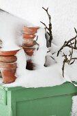 Verschneite Tontöpfe und Äste auf grünem Holztisch