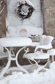 Reisigkranz an Fenster in Natursteinfassade, davor verschneiter Gartenmöbel