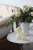 Kerze als Engelsfigur vor Krug mit trocknenden, weissen Rosen auf Vintage Metalltisch