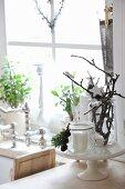 Weihnachtliche Deko auf Porzellan-Etagere, im Hintergrund Kerzenständer und Pflanztöpfe vor Fenster