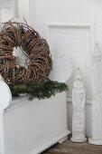 Geflochtener Kranz und Nadelbaumzweig auf altem Kastenstuhl, daneben stilisierte Nikolausfiguren