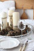 Tannenzapfen und geschmückte Kerzen auf silbernem Tablett auf gedecktem Tisch