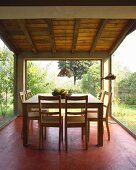 Moderner Essplatz auf rot gestrichenem Boden, Stühle und Tisch aus hellem Holz in rundum verglastem Raum, mit Blick in Garten