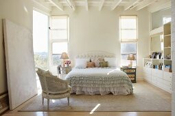 Rococo-style chair in front of double bed with ruffled bedspread in bright bedroom with white wooden ceiling