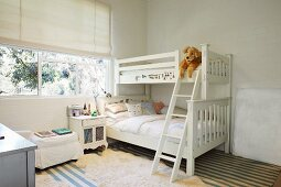 White bunk beds and bedside cabinet below window in children's bedroom