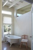 Free-standing, vintage bathtub next to window and below transom window in interior wall