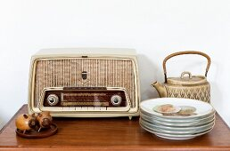 Still-life arrangement of flea-market finds; retro radio, teapot and stack of plates