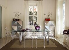 Dining set with glass table, Ghost chairs and half-height cabinets with shiny silver fronts with origami-style structures