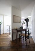 Simple, antique desk against slim partition and rustic wooden floor in designer interior