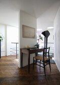 Schlichter, antiker Schreibtisch an schmalem Wandelement, rustikaler Dielenboden in Designerambiente