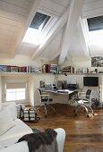 Schreibtisch mit Bürostühlen in modern ausgebautem Dachgeschoss mit rustikalem Dielenboden