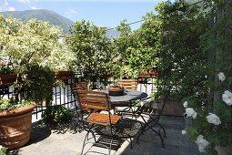 Sonnige Terrasse mit Tisch und Stühlen, Blumentöpfe auf Natursteinboden