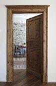 Traditionelle Kassettentür und Zarge mit Blick auf Essplatz vor Natursteinwand