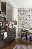Küche mit Edelstahlfront, im Hintergrund Natursteinwand und Essplatz
