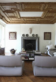 Grey, designer easy chairs in lounge area with open fireplace and partially coffered ceiling
