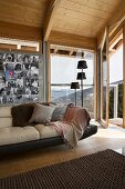 Leather sofa below collection of photos on wall next to group of standard lamps in front of panoramic window in wood-clad chalet interior