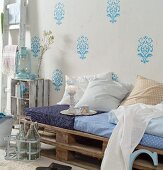 DIY couch upcycled from wooden pallets, seat cushions and scatter cushions against wall with light blue stencilled pattern