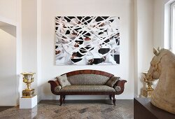 Postmodern sofa below modern painting on wall with elegant urn and stone horse head on plinth in elegant interior