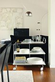 White crockery on retro-style serving trolley in open-plan interior with black furnishings and silver arc lamp