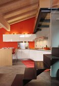 Open-plan, white designer kitchen with back wall painted deep orange in converted attic