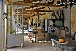 Partially renovated barn - kitchen area with free-standing counter, bar stools and curved vintage table in foreground in open-plan interior