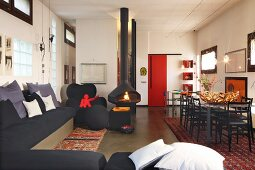 Comfortable, black corner sofa, suspended fireplace and dining area in open-plan, modern loft apartment