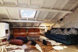Vintage Sitzgruppe mit abgewetzten Ledersesseln, Glastisch auf Gummirollen und kultigen Leuchtobjekten im Dachgeschosszimmer