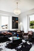 Crystal chandelier above classic leather sofa, cubic coffee table on cowhide rug and Baroque armchair