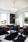 Kristallleuchter über klassischem Ledersofa, kubischer Coffeetable auf Kufellteppich und Barocksessel