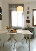 Dining area with laminated wood chairs, white-painted, country-house table and arc lamp